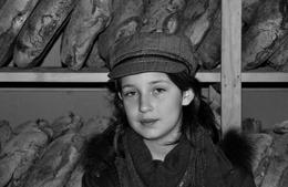 Menina com pão ao fundo